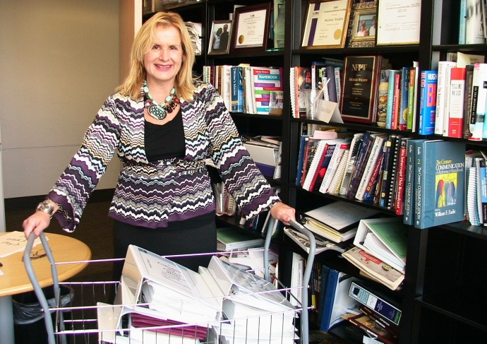 Michele Weldon stands in her office with all 8,000 pages of her tenure application.